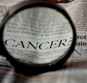 Loupe zoomant sur le mot cancer dans un journal