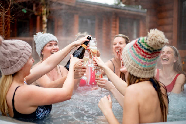 Groupe de femmes dans un jaccuzi qui trinquent au champagne