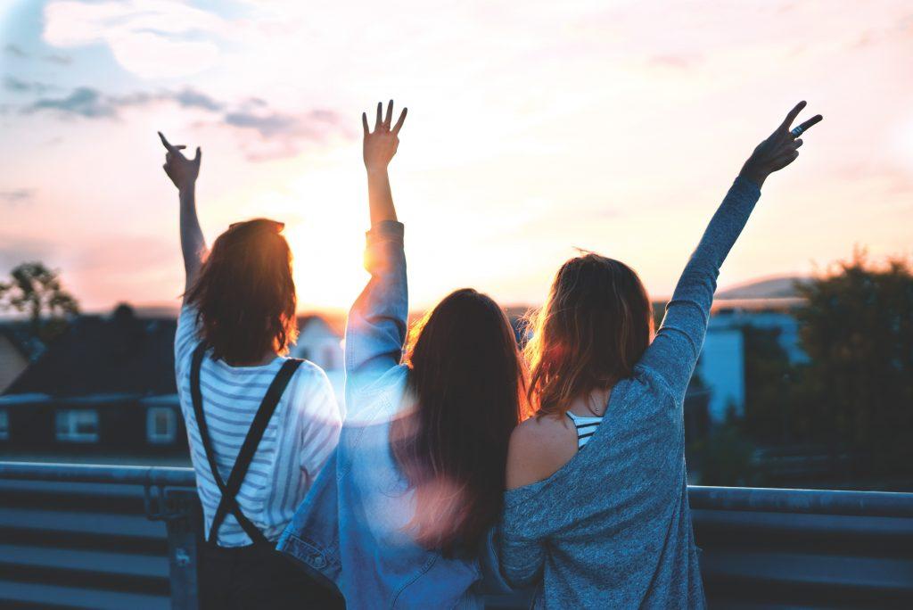 3 filles qui lèvent les bras avec vue sur une ville