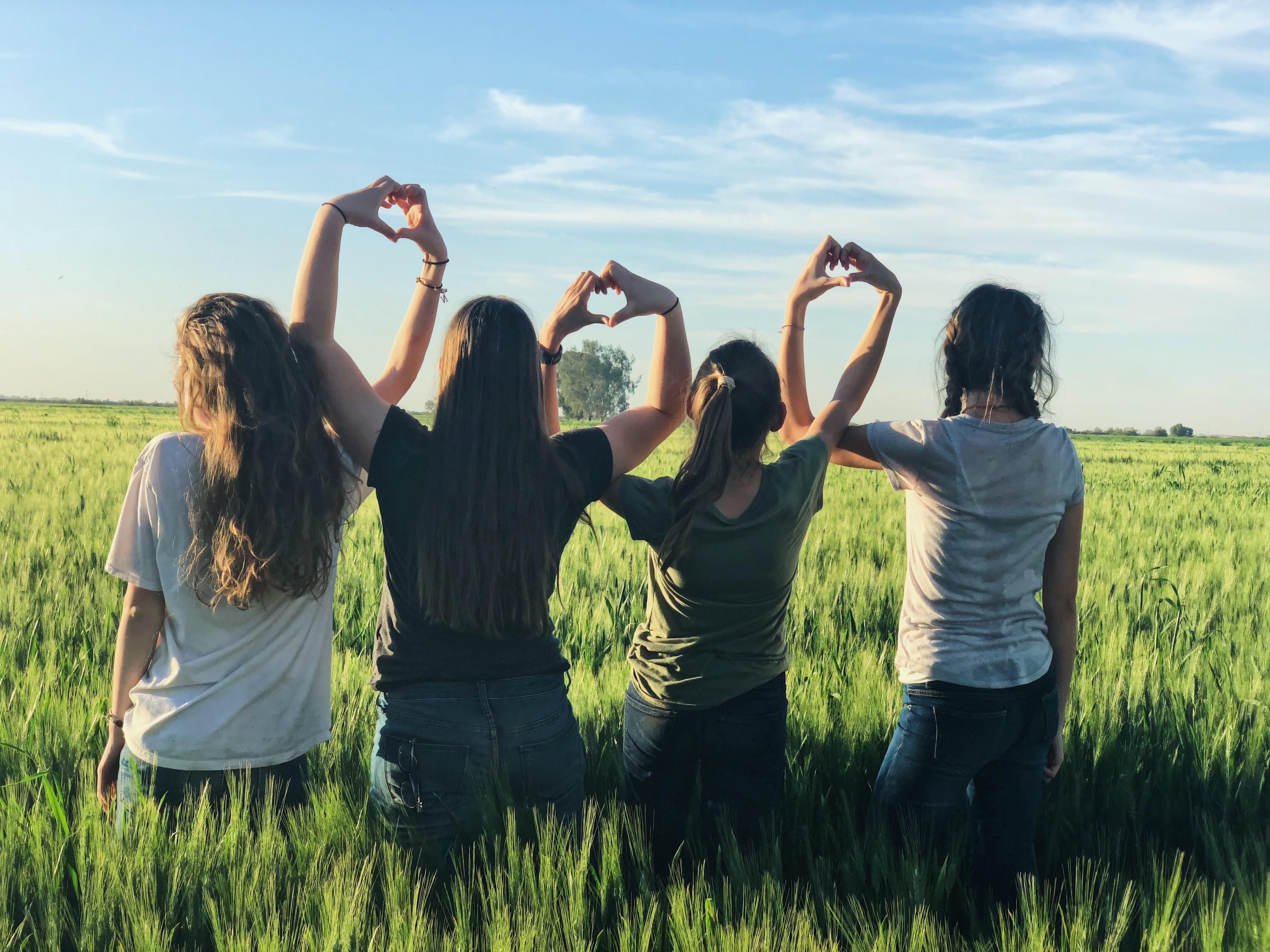 4 filles dans un champs qui forment des coeurs avec leurs mains