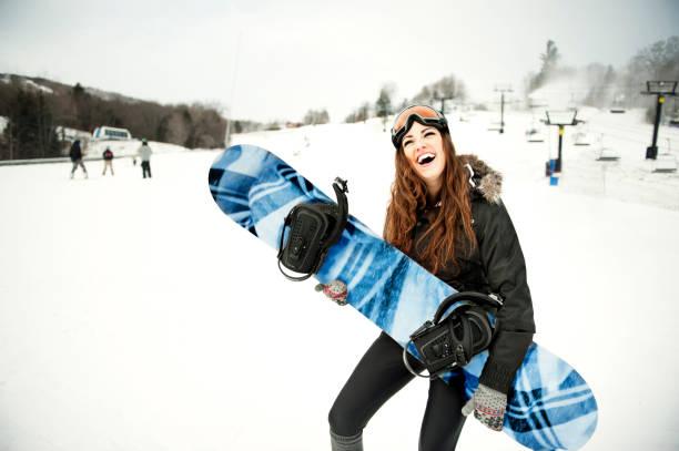 Jeune femme sur les pistes avec une planche de snowboard