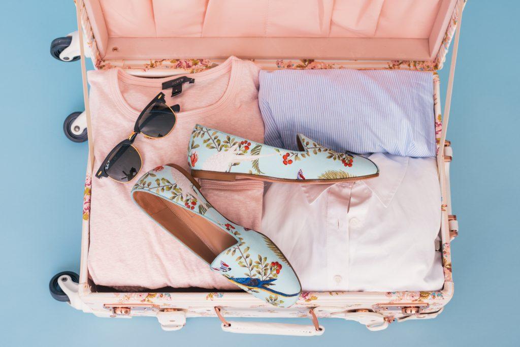 valise femme avec lunettes de soleil chaussures à fleurs et vêtements rose et bleu