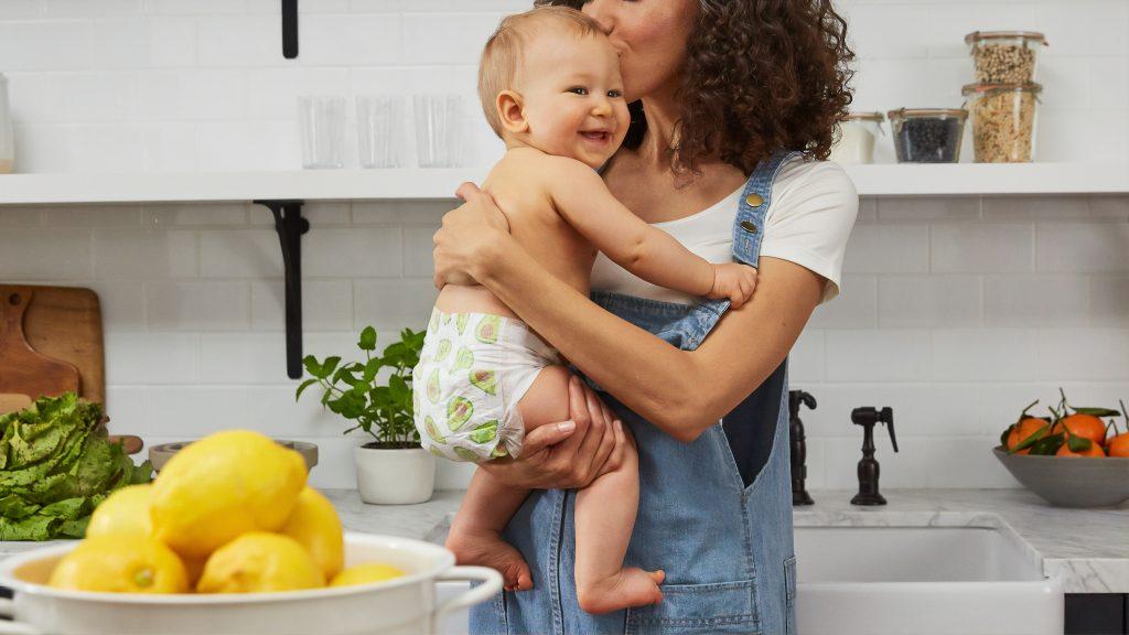 maman portant une salopette tenant son bébé en couche dans ses bras et lui faisant un bisou sur la tête
