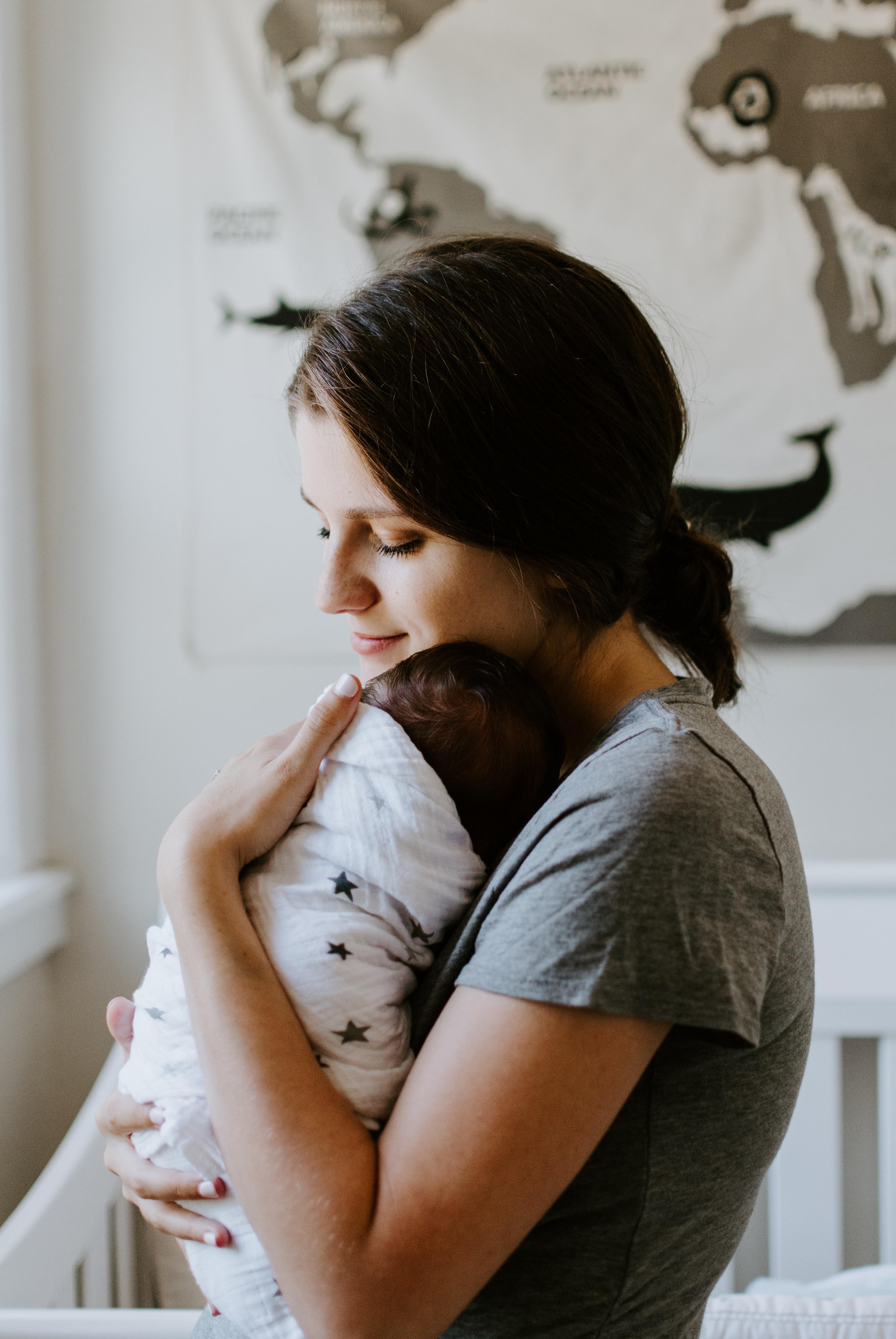 maman en t-shirt gris tenant son bébé recouvert d'une couverture dans ses bras