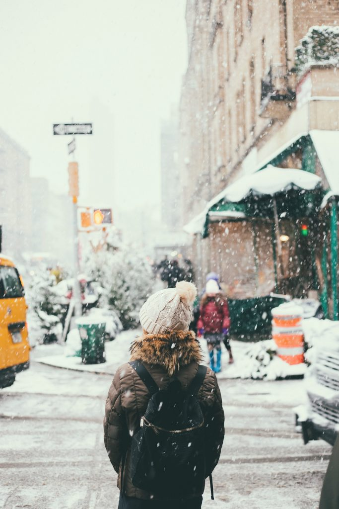 femme en ville sous la neige portant une doudoune un bonnet à pompon et une sac à dos noir