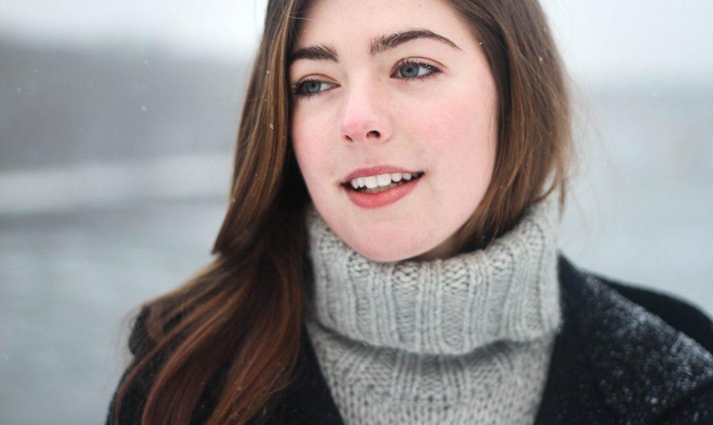 jeune femme portant un col roulé qui sourit