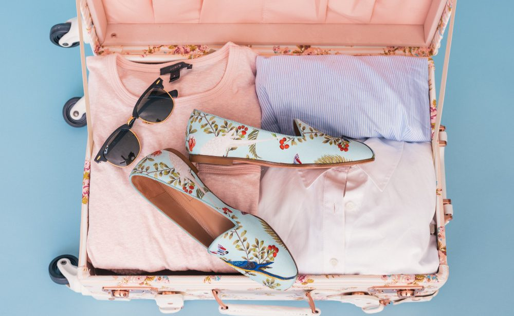 valise ouverte vue de dessus avec chaussures vêtements et lunettes de soleil