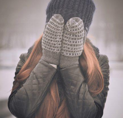 femme aux cheveux longs qui porte un bonnet et des moufles se cachant le visage