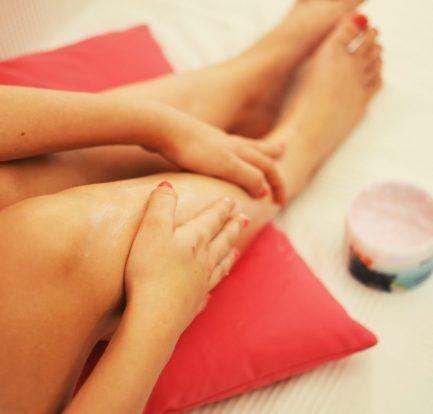 jeune femme qui met de la crême sur ses jambes épilées