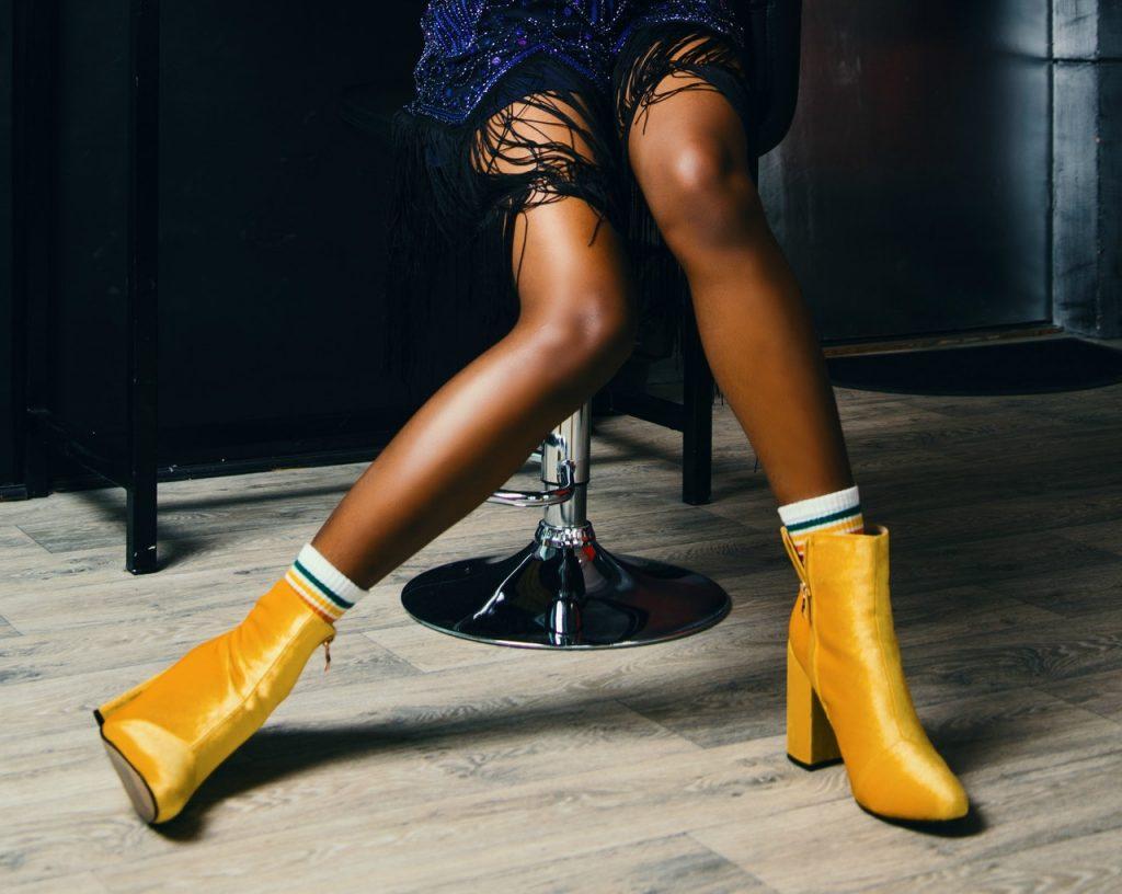 jambes d'une femme noire qui porte des bottines jaunes