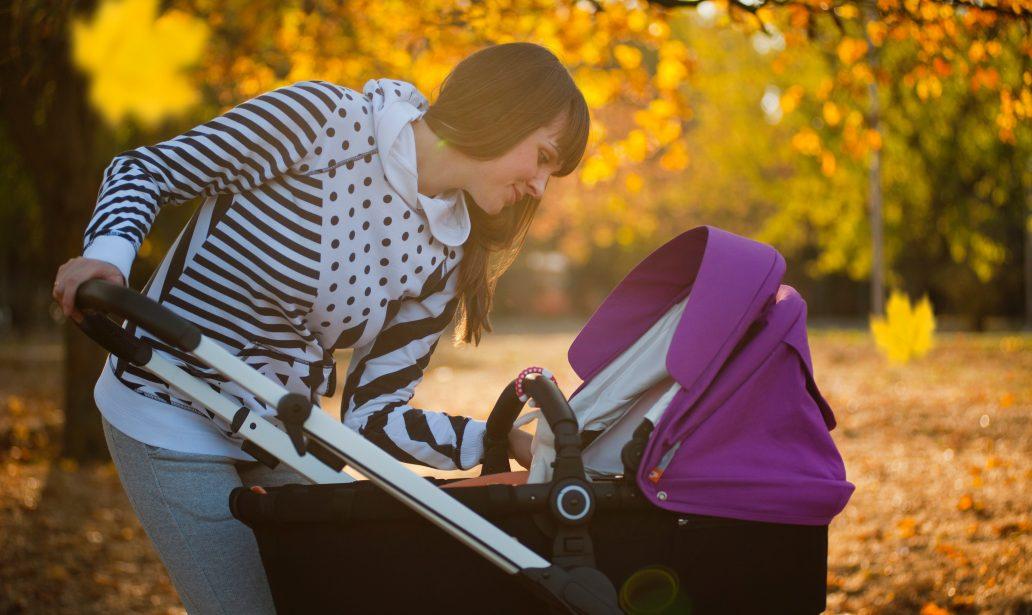 Jeune maman qui promène son bébé dans une poussette